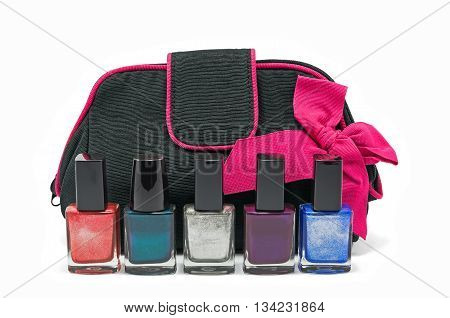 Black bag for cosmetics and accessories with a pink bow and bottles of multicolored nail polish isolated on a white background