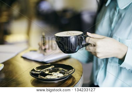 woman in holding a cup of cappuccino while writing