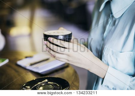 woman in blue shirt holding a cup of cappuccino