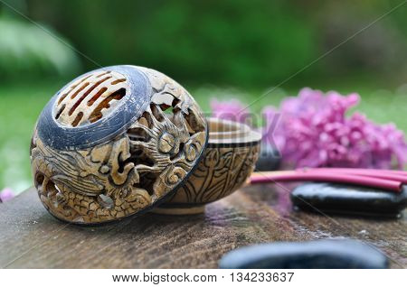 incense burner and stick with lilacs and pebble on a plank in garden