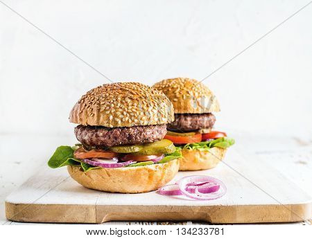 Fresh homemade burgers on wooden serving board with onion rings. White background, selective focus, copy space
