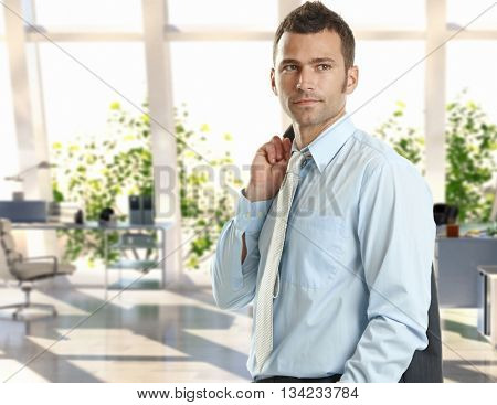 Confident young caucasian handsome businessman standing at bright office. Suit and tie.