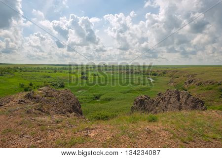 Wonderful scenery - marshy river with steep banks in the prairie. Sunny day in countryside. Ukraine. Toned image.