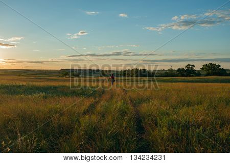 Woman with dog go to the sunset on the prairie desert. Azov steppes Ukraine. Wide angle.