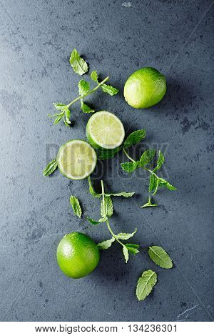 Fresh Limes and Mint Leaves on a Black Stone