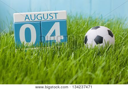 August 4th. Image of august 4 wooden color calendar on green grass lawn background with soccer ball. Summer day. Empty space for text.