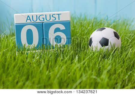 August 6th. Image of august 6 wooden color calendar on green grass lawn background with soccer ball. Summer day. Empty space for text.