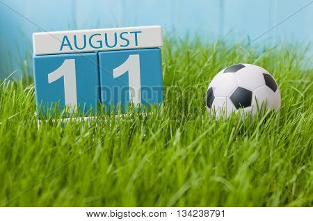 August 11th. Image of august 11 wooden color calendar on green grass lawn background with soccer ball. Summer day. Empty space for text.