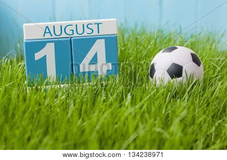 August 14th. Image of august 14 wooden color calendar on green grass lawn background with soccer ball. Summer day. Empty space for text.