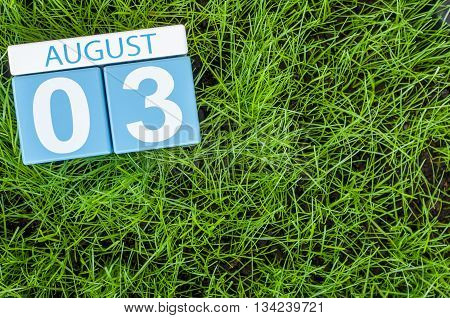 August 3rd. Image of august 3 wooden color calendar on green grass lawn background. Summer day. Empty space for text.