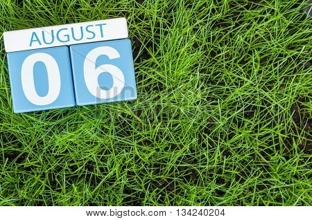 August 6th. Image of august 6 wooden color calendar on green grass lawn background. Summer day. Empty space for text.