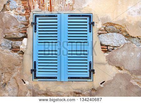 little window with blue shutters on a decrepit wall