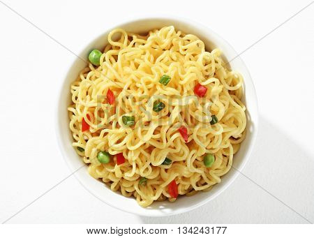 Vermicelli with green peas and chopped bell pepper in white bowl on white background. Close up top view high resolution product.