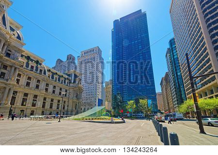 Philadelphia, USA - May 5, 2015: Penn Square with Philadelphia City Hall and skyline of skyscrapers. Tourists on the square. Pennsylvania USA. With special sun flare