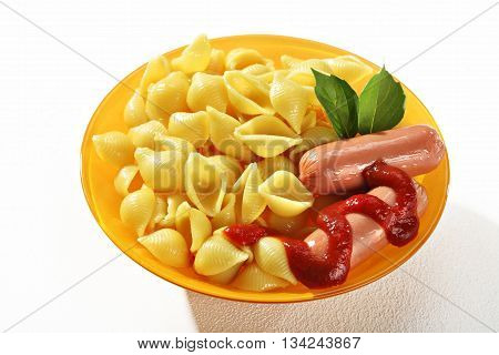 Cooked macaroni shells with sausages and sauce in orange plate on white background. Close up high resolution product.
