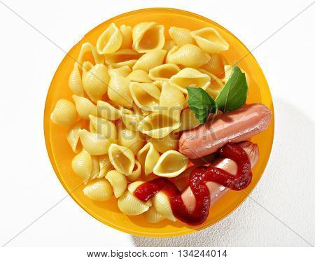 Expertly cooked macaroni shells with sausages in orange plate on white background. Close up top view high resolution product.