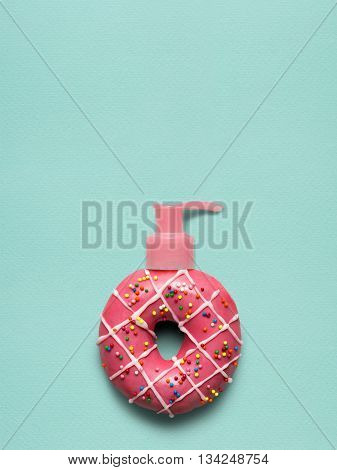 Creative still life of a tasty sweet donut with a cosmetic pump dispenser on blue background.