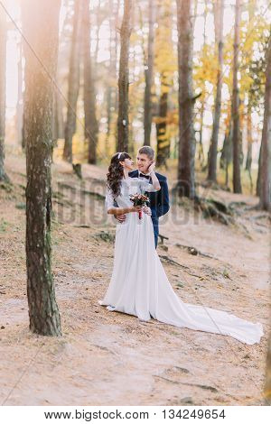 Happy romantic newly married couple holding each other in the autumn pine forest.