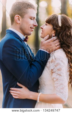 Happy romantic newly married couple before the kiss in the autumn pine forest.