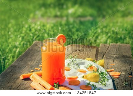 Carrot juice in jar - refreshing drink on rustic table
