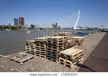 Pallets on the quay side in Rotterdam with the Erasmus bridge in the background