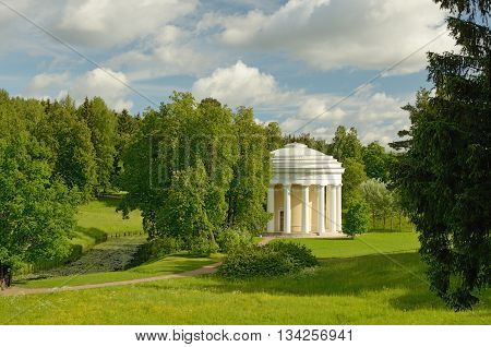 Russia.Pavlovsk.Country Park with a rotunda.Around a lot of vegetation.Blue sky oblakami.