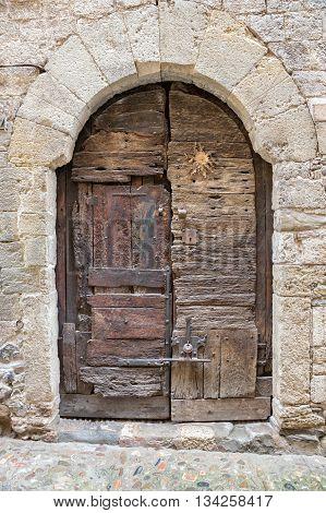 Antique wooden door in the medieval village of Besalu in Catalonia Spain.