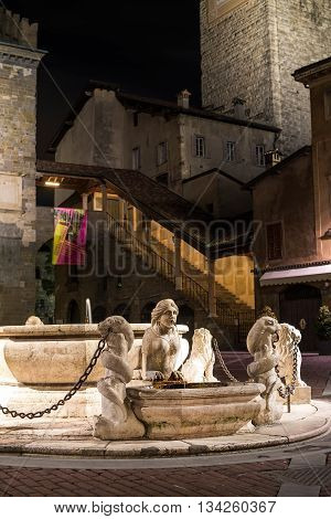 BERGAMO, ITALY - 14, JANUARY. Central square of medieval town with fontaine in evening. Taken on Piazza Veccia in Bergamo, Citta Alta, Lombardia, in winter, 2016