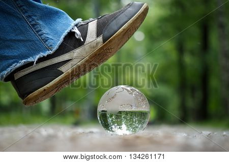 Transparent ball under dirty sneakers. The path, the forest. The boot falls on the fragile balloon. Concept, idea