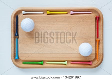 Cutting board with different wooden golf tees and golf balls