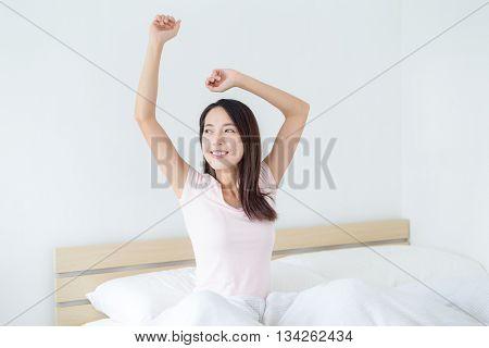 Woman wake up and raising hand up