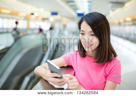 Woman use of mobile phone at train station