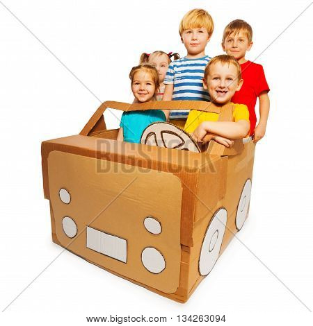 Picture of five happy preschoolers driving toy handmade cardboard car, isolated on white background