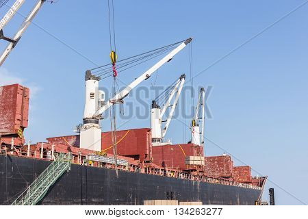 Commercial Ship With Cranes While Unloading Container To The Ship