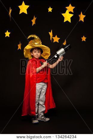 Full length photo of boy playing stargazer with a telescope, standing against black background with paper stars above