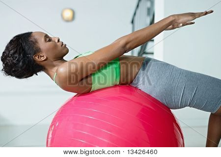 African Woman Doing Series Of Sit-ups In Gym