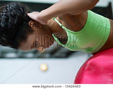 Mulher africana malhando na Fitball em ginásio