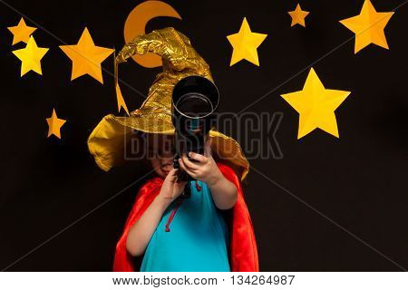 Little child in sparkling cap and red hood looking through a telescope at the starry dark sky background