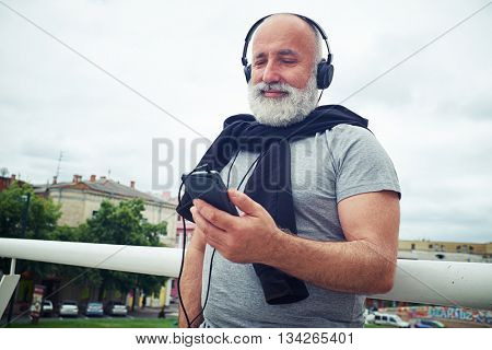 Stylish aged man in casual clothes is standing near handhold on the bridge wearing headphones connected to his smart phone