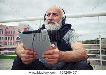 Stylish aged man in headphones is sitting on a sidewalk on a cloudy day with tablet computer in his hands and musing