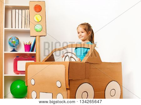 Cute little girl driving her toy cardboard car at the kindergarten