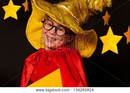 Close up picture of five years old boy in glasses and sky watcher costume against starry night sky