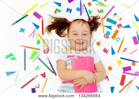 Close-up photo of laughing preschool girl holding pink book, laying among school office supplies