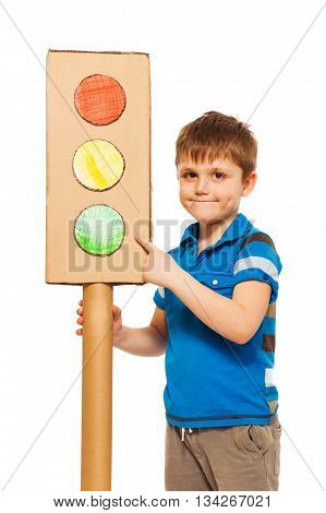 Kid boy studying road traffic regulations, pointing to the green light of cardboard lights model, isolated on white