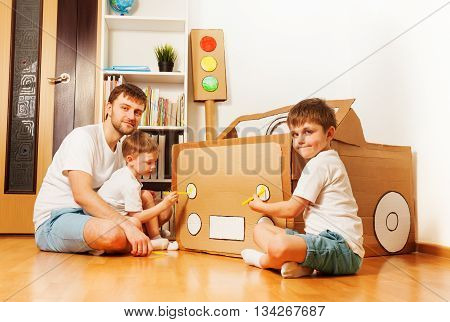 Two kid boys with their father painting headlights on toy cardboard car with yellow felt-tip pens at the room
