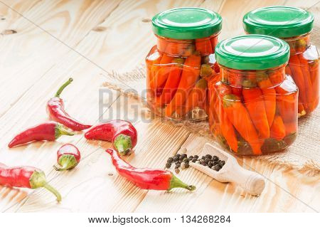 preserved chili pepper in glass jars on wooden table covered sackcloth jars pepper wooden scoop copy space. free space for text