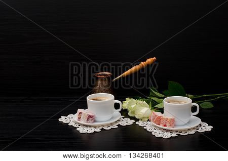 A couple cups of coffee with milk Cezve Turkish Delight a bouquet of white roses on a black background. Space for text