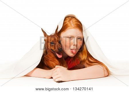 Young girl under the white blanket with her pet dog smile and happy put out tongue
