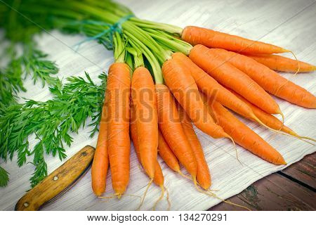 Fresh organic carrots on rustic wooden table
