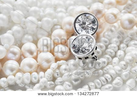 Diamond earrings and strings of pearl as a background